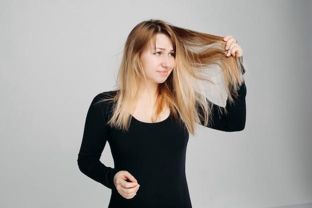 1つの手で厄介な髪と別の1つでヘアブラシを保持しているきれいな女性