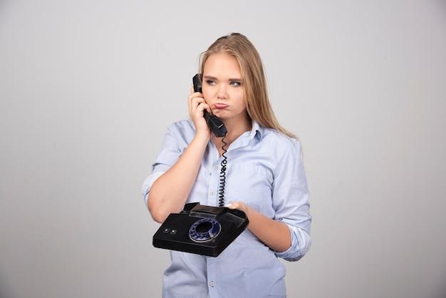 전화를 들고 외진 회색 벽을 말하는 예쁜 여자.