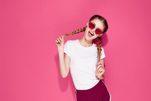 ピンクの背景をポーズするおさげの夏のファッション服を保持しているきれいな女性