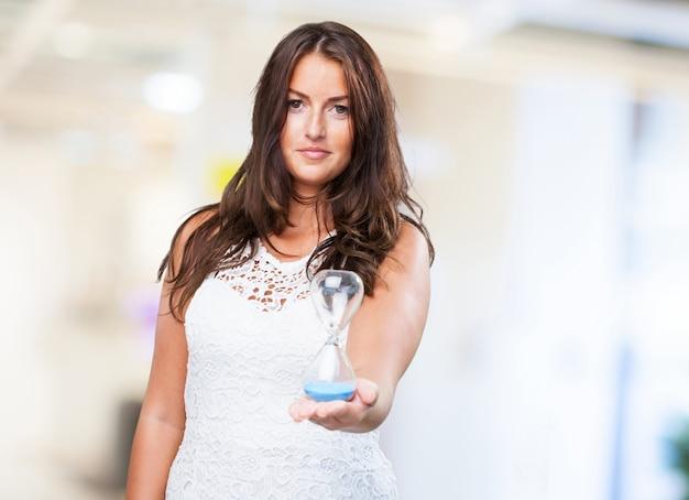 Pretty woman holding a sandtimer