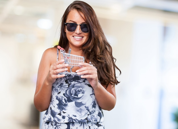 Pretty woman holding a shopping cart