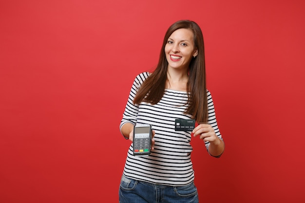 Pretty woman holding wireless modern bank payment terminal to process and acquire credit card payments, black card isolated on red background. people sincere emotions, lifestyle. mock up copy space.