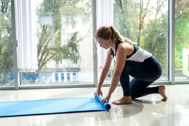 ジムの窓の前に立って運動する前にヨガの敷物を保持しているきれいな女性