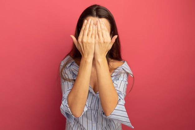 La donna graziosa tiene le mani davanti alla faccia isolata sulla parete rosa
