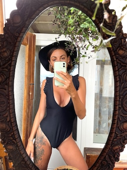 Pretty woman at home takes photo selfie in mirror on mobile phone for stories and posts in social media, wearing black summer swimsuit