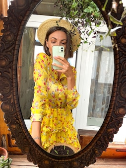 Pretty woman at home takes photo selfie in mirror on mobile phone for stories and posts in social media,