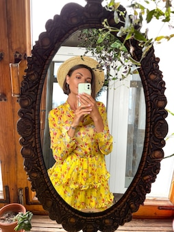 Pretty woman at home takes photo selfie in mirror on mobile phone for stories and posts in social media