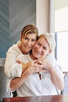シニアの母親を抱いてきれいな女性