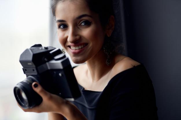 ファッションモデルをポーズする窓の近くの黒いドレスを着たきれいな女性。高品質の写真