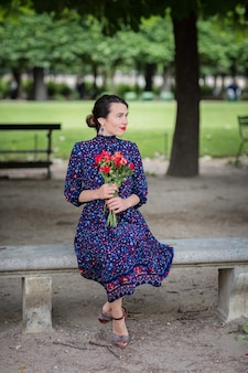 公園の椅子に座っている紺色のドレスを着たきれいな女性