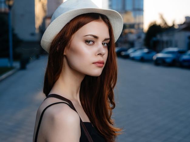 夏のポーズを屋外で帽子をかぶったきれいな女性。高品質の写真