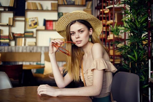 모자에 예쁜 여자는 배경 클로즈업에서도 서와 함께 테이블에 앉는 다.