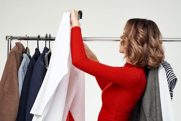 Красивая женщина в красной куртке возле шкафа изолированного фона