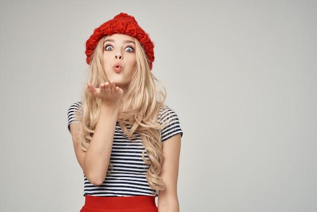 縞模様のtシャツの赤い帽子の明るい背景のライフスタイルのきれいな女性