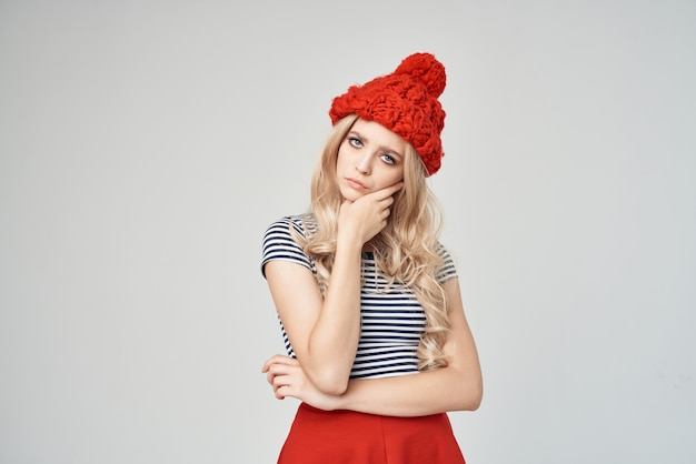 縞模様のtシャツの赤い帽子のポーズスタジオのきれいな女性