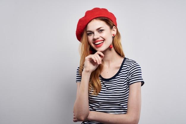 縞模様のtシャツの赤い唇のジェスチャーで彼の手が分離された背景を持つきれいな女性