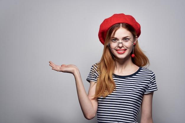 彼の手のライフスタイルで縞模様のtシャツの赤い唇のジェスチャーできれいな女性