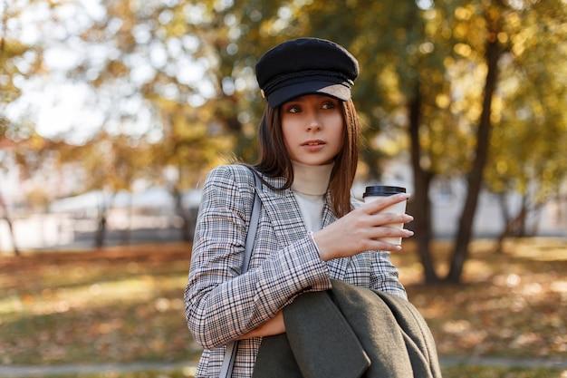 Красивая женщина в стильной кепке с модным костюмом держит в руках пальто и вкусный кофе и гуляет в осеннем парке
