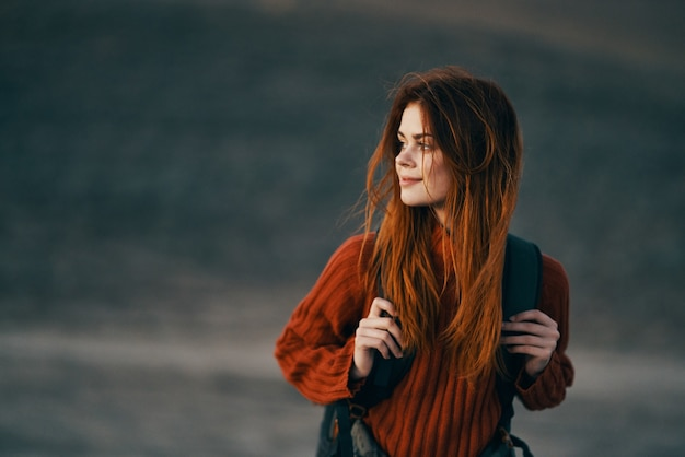 バックパックとセーターを着たきれいな女性が牧草地の山の中を自然の中を歩いています