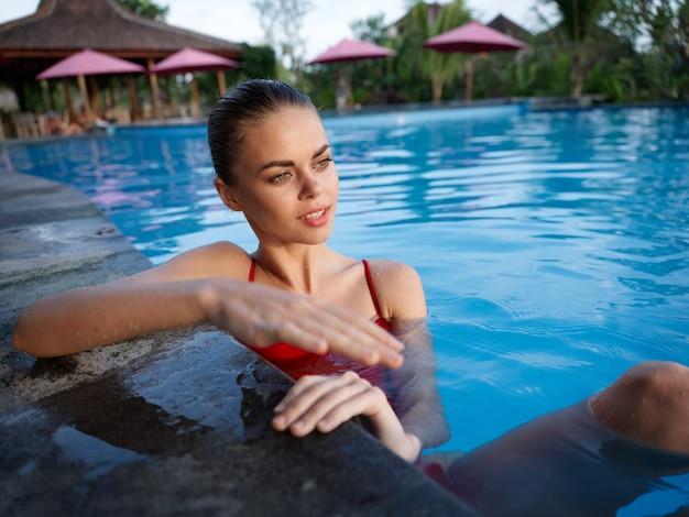 プールのタイルに寄りかかって水着姿のきれいな女性澄んだ水夏休みリラックス