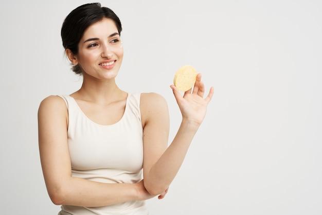 Красивая женщина в белой футболке губка в руках чистит лицо