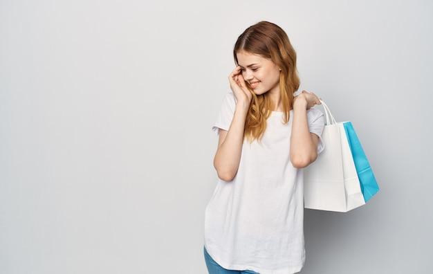 쇼핑 손에 패키지와 흰색 티셔츠에 예쁜 여자
