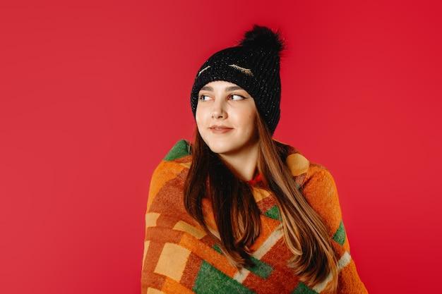 暖かい格子縞に包まれて横を向いている冬の帽子をかぶったきれいな女性