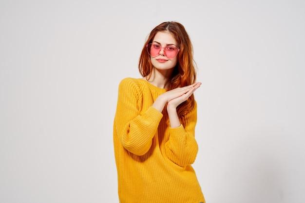 スタジオの楽しいモデルをポーズする黄色いセーターの髪型のきれいな女性。高品質の写真