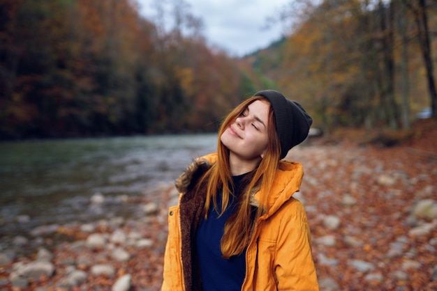 森の川の落ち葉で秋の服を着たきれいな女性