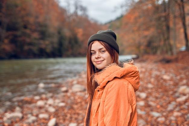 川の横で秋の服を着たきれいな女性