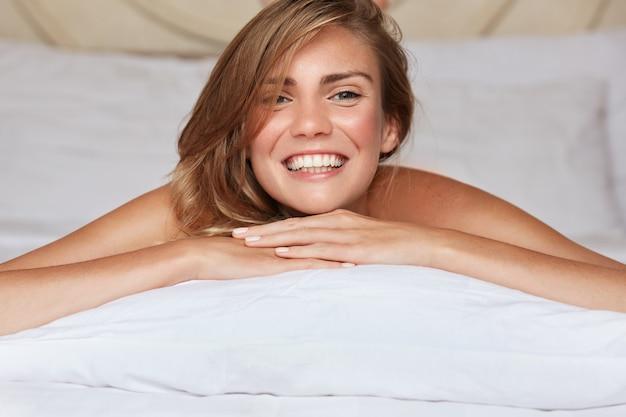 枕の上に座ってベッドのきれいな女性