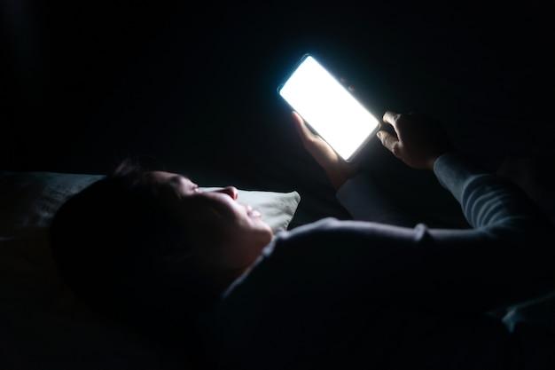 暗い寝室で夜遅くにスマートフォンを使用してベッドできれいな女性。携帯電話中毒の概念