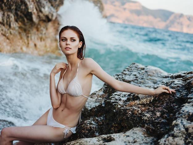 ビキニのきれいな女性は、風景の海の波を揺るがします