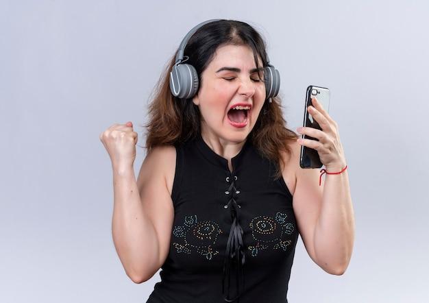 ヘッドフォンで音楽を聴いて踊る電話を保持している黒いブラウスのきれいな女性