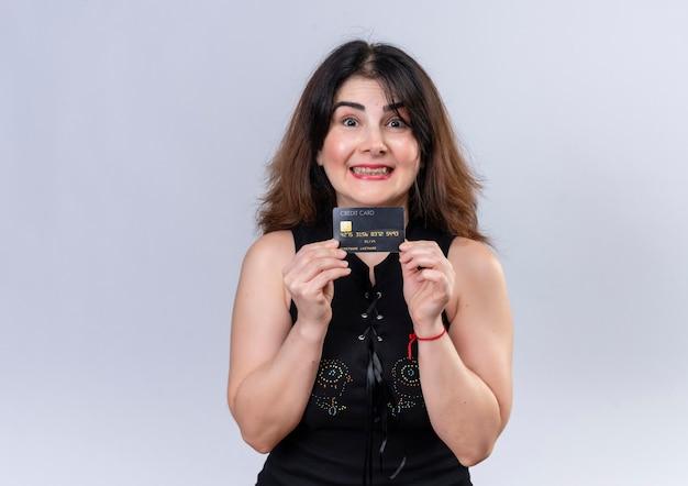 クレジットカードでカメラを喜んで見ている黒いブラウスのきれいな女性