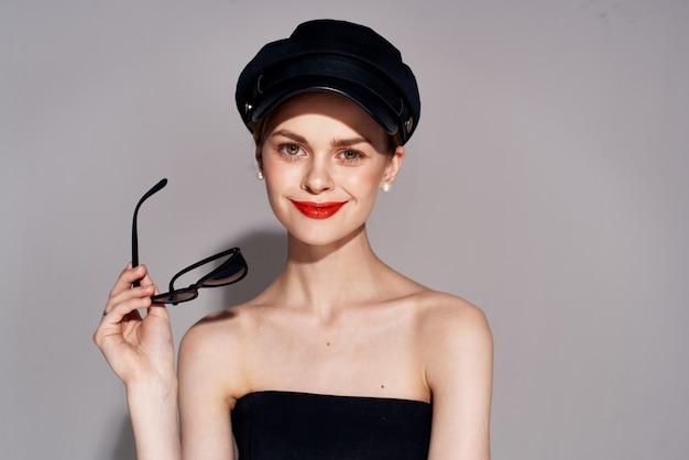 化粧品の魅力のトリミングされたビューの手にサングラスをかけた黒のドレスのきれいな女性。