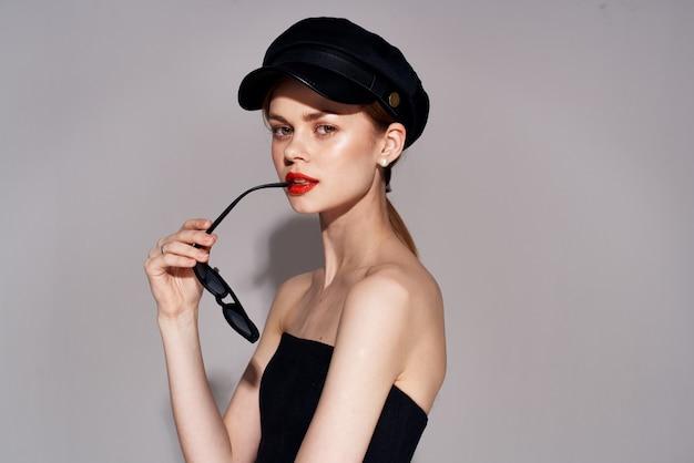 黒帽子サングラスイブニングドレスのクローズアップのきれいな女性。