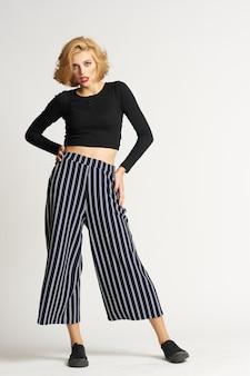 黒のセーターストライプパンツファッション服明るい背景スタジオのきれいな女性。