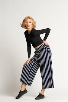 黒のセーターストライプパンツファッション服ライトスタジオのきれいな女性。