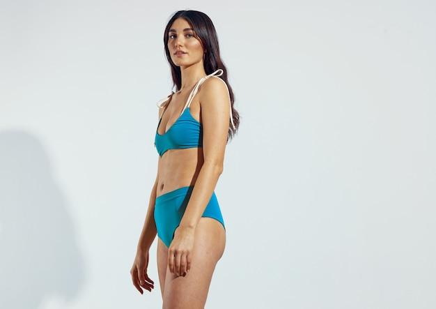 Красивая женщина в голубых купальниках бикини позирует на пляже