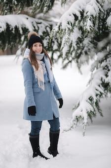 Красивая женщина в синем пальто гуляет по лесу в зимний снежный день