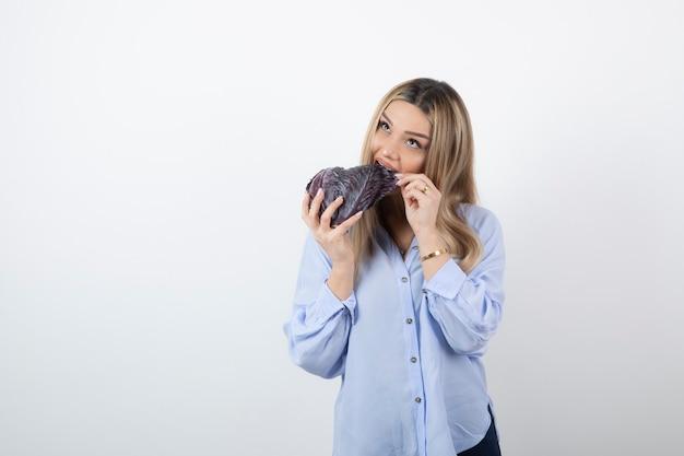 Красивая женщина в синем наряде ест фиолетовую капусту на белом фоне.