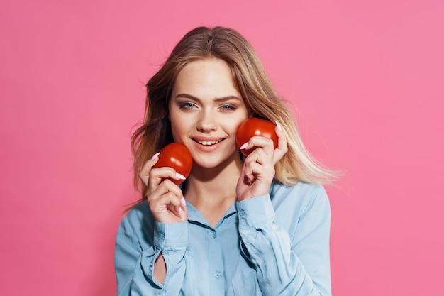 彼女の手の食べ物にトマトと青いシャツのきれいな女性