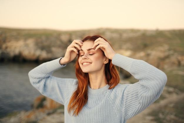 青いセーターのきれいな女性は自然の新鮮な空気の自由をお楽しみください