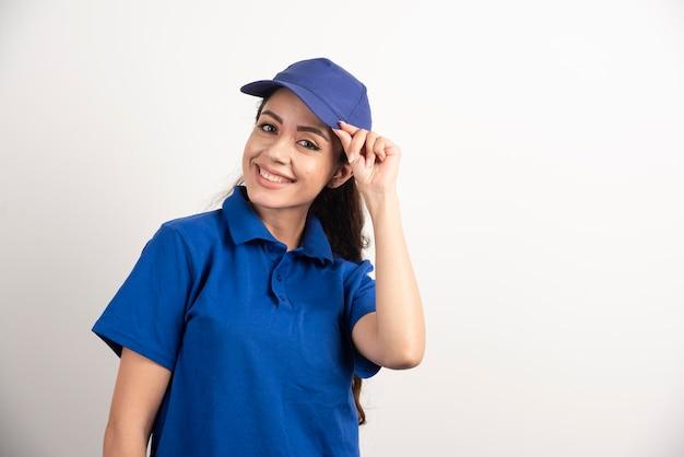 青い制服を着た可愛い女性が手で顔を触る。高品質の写真