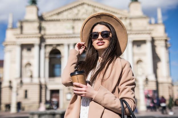 彼女の手でコーヒーカップが付いている都市でポーズをとってカジュアルな秋服のきれいな女性