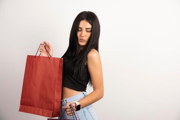 ショッピングバッグを持っているカジュアルな服装のきれいな女性。高品質の写真