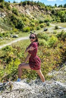 自然の中でポーズ、夏の晴れた日シックな赤い市松模様のドレスのきれいな女性