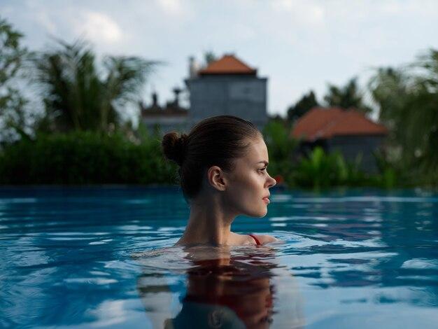 澄んだプールの水とモデルのトリミングされたビューのきれいな女性