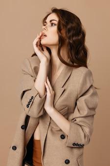 Красивая женщина в пальто держит руки возле модели косметики очарования лица